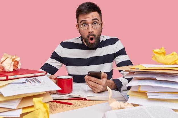 Geschokt verbaasd jonge blanke man gebruikt moderne mobiele telefoon, drinkt koffie, schrijft records in kladblok, bestudeert papieren met afbeeldingen