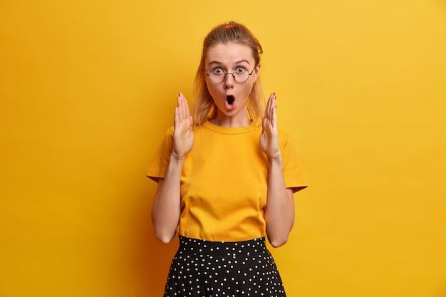 Geschokt verbaasd vrouwelijk model meet iets heel groots, demonstreert een enorm item met handen dat de mond openhoudt van verrassing