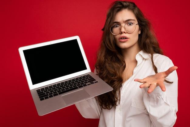 Geschokt verbaasd zonder mooie brunette krullend jonge vrouw sayong wow computer laptop dragen van een bril wit overhemd kijken camera geïsoleerd over rode muur achtergrond. bespotten