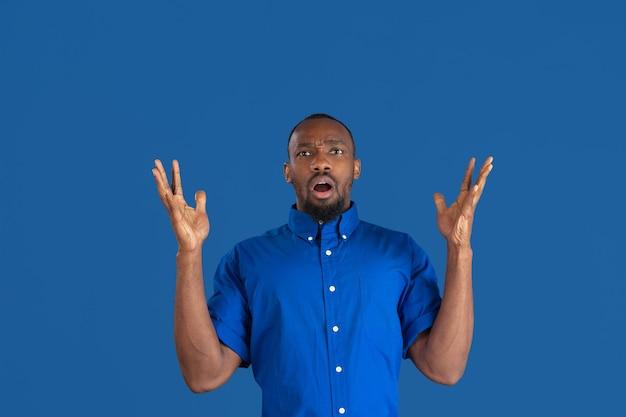 Geschokt, verbaasd. zwart-wit portret van jonge afro-amerikaanse man geïsoleerd op blauwe muur. mooi mannelijk model. menselijke emoties, gezichtsuitdrukking, verkoop, advertentieconcept. jeugd cultuur.