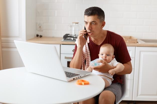 Geschokt verbaasde donkerharige knappe man met een casual t-shirt met een handdoek op zijn schouder, aan tafel zitten met laptop, babymeisje in handen houdend, telefoon pratend en kijkend naar de weergave van een notebook.