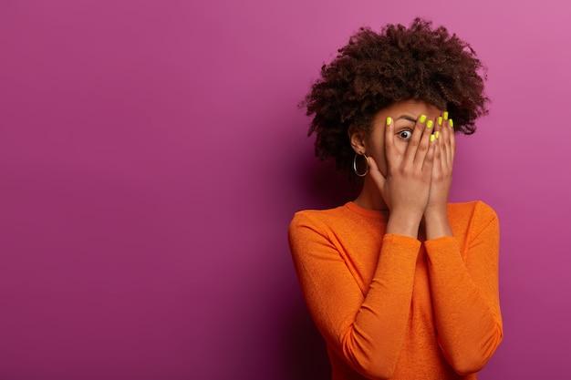 Geschokt verbijsterde afro-amerikaanse vrouw verbergt gezicht met beide handpalmen