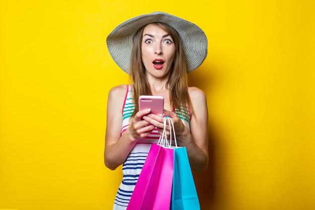 Geschokt verrast jong meisje met boodschappentassen met een telefoon