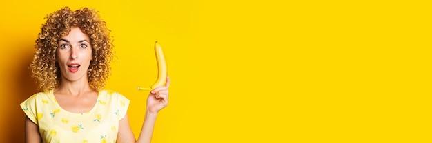 Geschokt verrast krullend jonge vrouw met een banaan op een gele achtergrond.