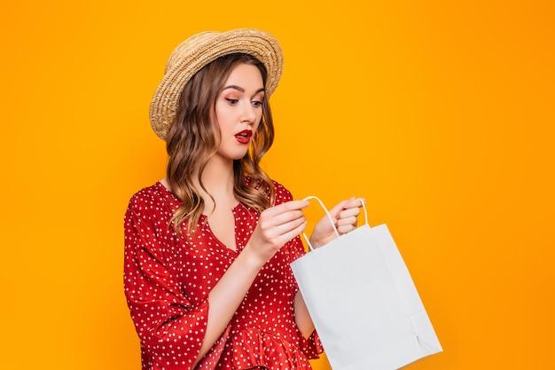 Geschokt verrast meisje dragen in een rode zomerjurk en strooien hoed met rode lippen kijkt in een boodschappentassen geïsoleerd over oranje muur