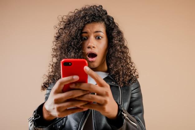 Geschokt verrast zwart meisje die haar telefoonscherm bekijken dat over bruin wordt geïsoleerd