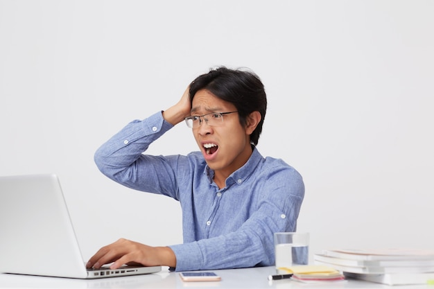 Geschokt verward aziatische jonge zakenman in glazen met hand op het hoofd en geopende mond werken met laptop aan de tafel over witte muur