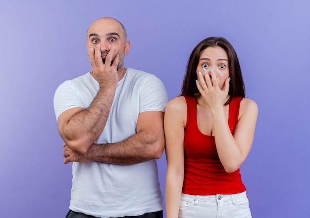 Geschokt volwassen paar dat hand op mond kijkt