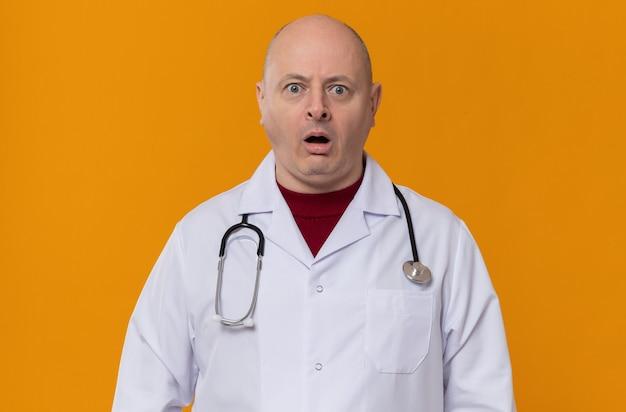 Geschokt volwassen slavische man in doktersuniform met stethoscoop kijkend naar voren