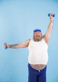 Geschokt volwassen zwaarlijvige man met baard doet oefeningen met halters die hard trainen op een lichtblauwe achtergrond in de studio