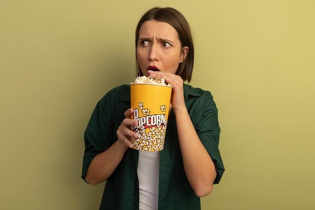 Geschokt vrij blanke vrouw eet en houdt emmer popcorn kijken kant op olijfgroen