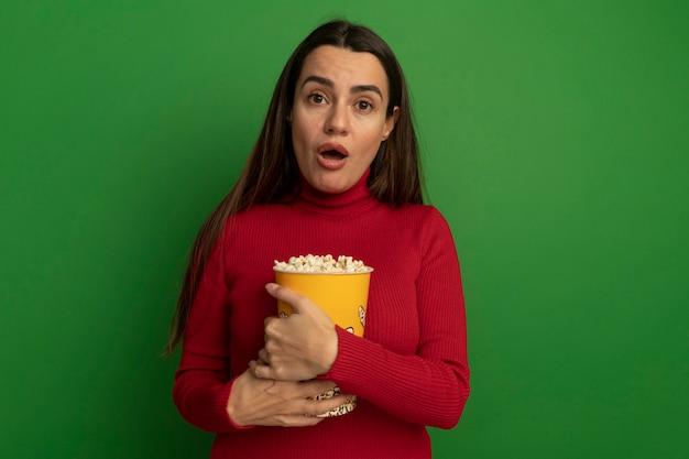 Geschokt vrij blanke vrouw houdt emmer popcorn op groen
