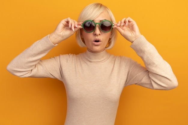 Geschokt vrij blonde slavische vrouw kijkt camera door zonnebril op oranje