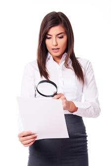 Geschokt vrouw die door een vergrootglas op documenten kijkt