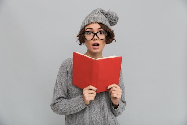 Geschokt vrouw gekleed in trui en warme muts bedrijf boek.