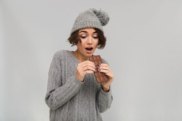 Geschokt vrouw gekleed in trui en warme muts bedrijf chocolade.