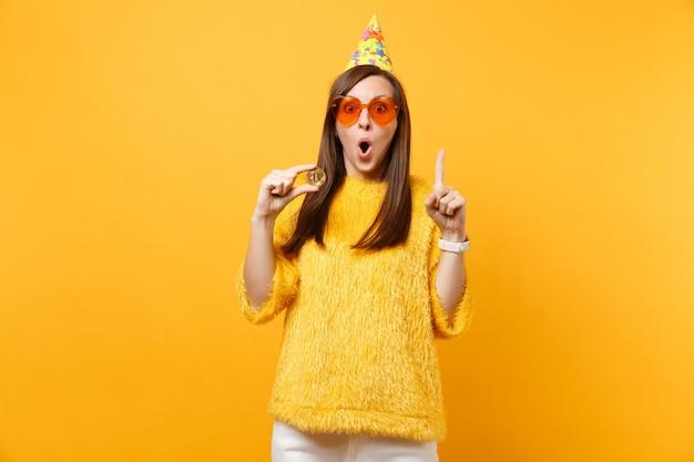 Geschokt vrouw in oranje hart glazen verjaardag hoed wijzende wijsvinger omhoog met bitcoin metalen munt van gouden kleur toekomstige valuta geïsoleerd op gele achtergrond. mensen oprechte emoties levensstijl.