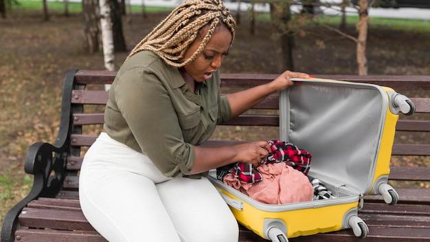 Geschokt vrouw kijkt door haar geopende bagage