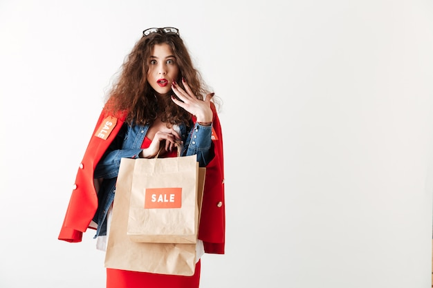 Geschokt vrouw met papieren boodschappentassen