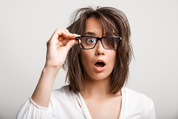 Geschokt vrouw met warrige rommelig kapsel kijken door een bril