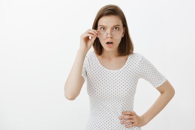 Geschokt vrouw opstijgen bril en op zoek dichterbij met verward gezicht