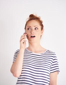 Geschokt vrouw praten door mobiele telefoon schot