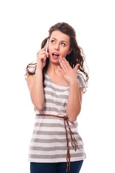 Geschokt vrouw praten via de mobiele telefoon
