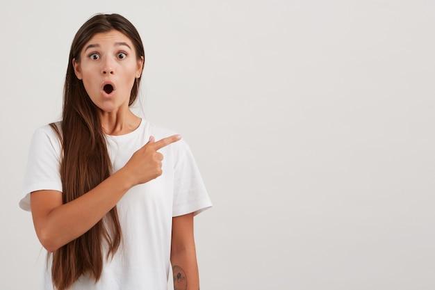 Geschokt vrouw, verrast meisje met donker lang haar, wit t-shirt dragen en heeft tatoeage