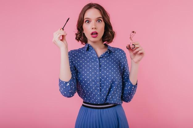 Geschokt vrouwelijk model in blauwe kledij poseren met mascara in de hand. mooie verbaasde vrouw krult haar wimpers.