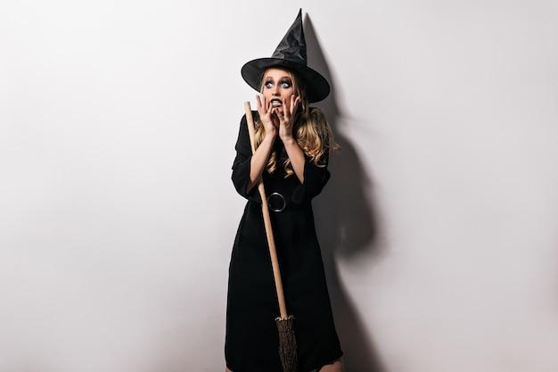 Geschokt vrouwelijk model in tovenaarskostuum poseren op witte muur. binnen schot van verbaasd heksenmeisje dat zich met bang gezichtsuitdrukking bevindt.