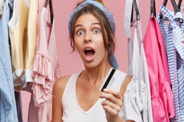 Geschokt vrouwtje in wit t-shirt, staande in de buurt van een kledingrek, met creditcard, verbaasd dat ze geen geld heeft voor haar accountant en haar garderobe wil opfrissen. outfit kopen