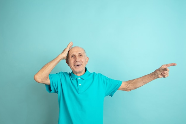 Geschokt wijzend naar de zijkant. kaukasische senior man portret op blauwe studio.