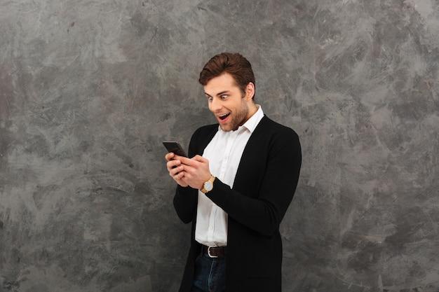 Geschokt zakenman chatten via de mobiele telefoon.