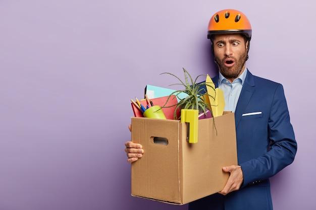 Geschokt zakenman poseren in stijlvol pak en rode helm op kantoor
