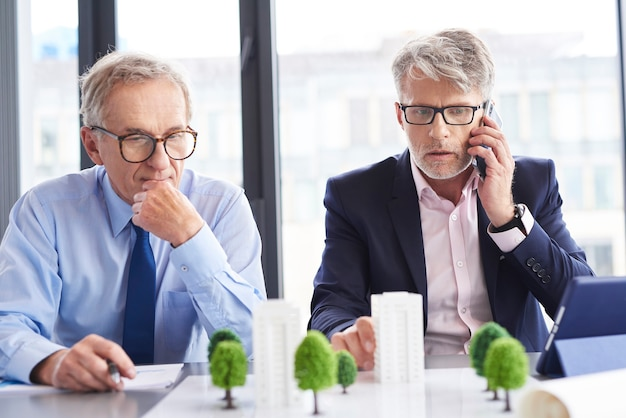 Geschokt zakenman praten via de mobiele telefoon tijdens zakelijke bijeenkomst
