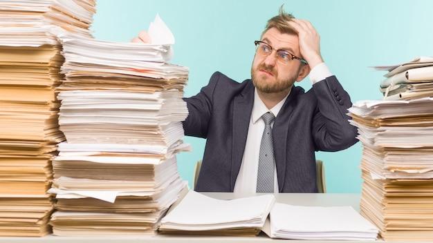 Geschokt zakenman zit aan de tafel met veel papieren in kantoor, hij is overladen met werk - imago