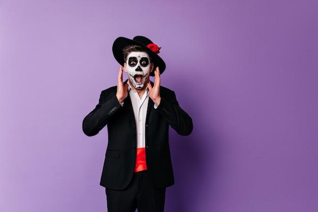Geschokt zombiemens in elegante kleding die zich voordeed op paarse achtergrond in halloween. verrast man in mexicaanse outfit viert de dag van de doden.