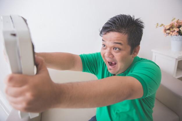 Geschokt zwaarlijvige man tijdens het kijken naar een weegschaal