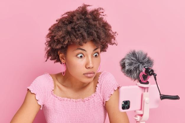 Geschokte afro-amerikaanse vrouw met krullend haar staart naar telefoon webcam registreert livestream video heeft online trainingen