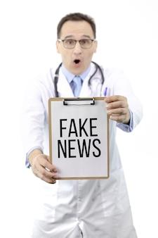 Geschokte arts houdt klembord met tekst nepnieuws. sterfte medische statistieken