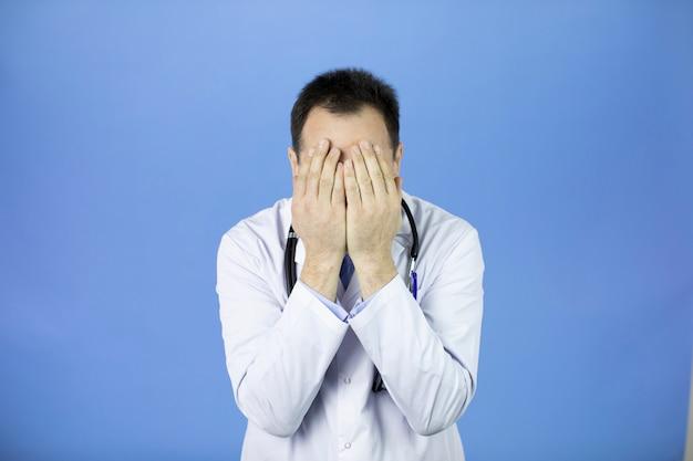 Geschokte arts van middelbare leeftijd die gezicht met handen behandelt wegens vergissing, vermoeidheid