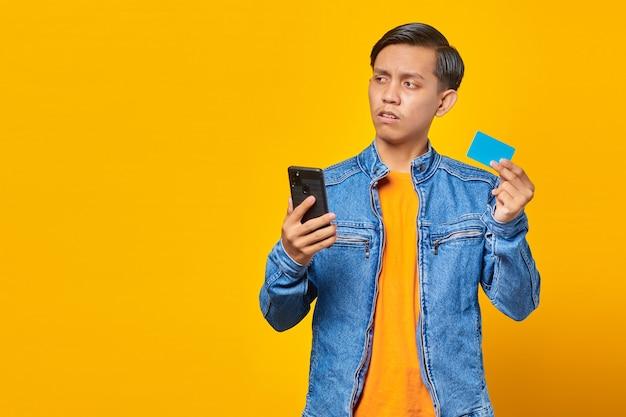 Geschokte aziatische man die mobiele telefoon vasthoudt en creditcard toont over gele achtergrond