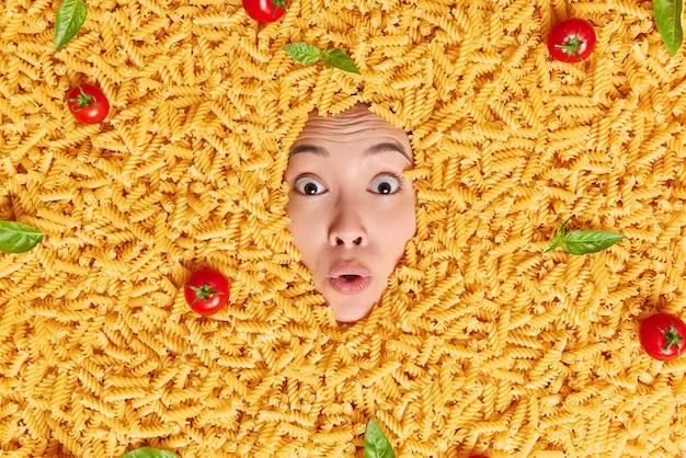 Geschokte aziatische vrouw begraven in ongekookte macaroni heeft wijd opengesperde ogen omringd door rode tomaten en groene basilicumbladeren, stomverbaasd om iets geweldigs te horen Premium Foto