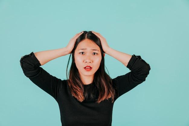 Geschokte aziatische vrouw die camera bekijkt