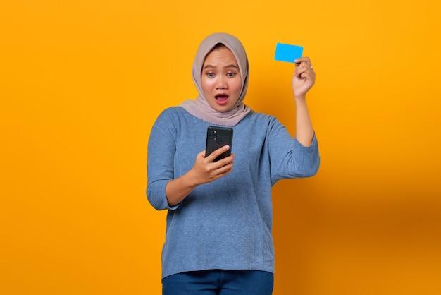 Geschokte aziatische vrouw die mobiele telefoon vasthoudt en creditcard toont over gele achtergrond