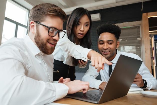 Geschokte aziatische vrouw die vertoning van laptop computer toont aan haar collega's