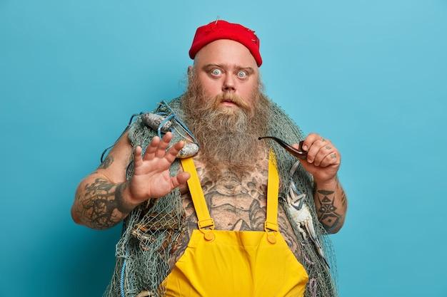 Geschokte bange zeeman of visser houdt handpalm in afwijzingsgebaar, schrikt van iets vreselijks, poseert met vistuig, vangt vis in zee, houdt rookpijp vast