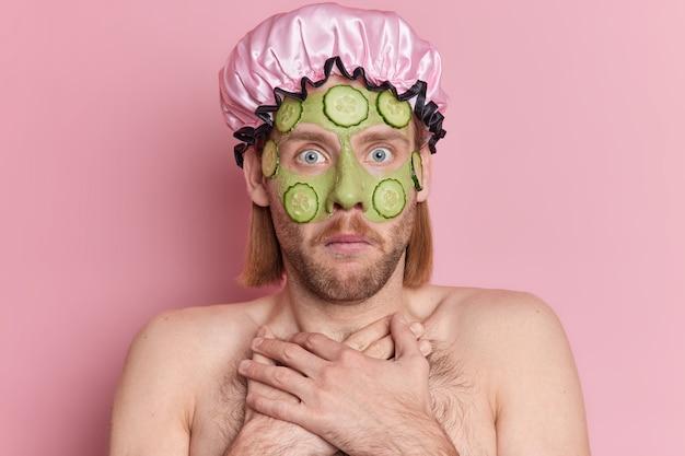 Geschokte bebaarde europese man staart afgeluisterde ogen houdt handen op de borst past groen voedend masker met plakjes komkommer draagt badmuts.