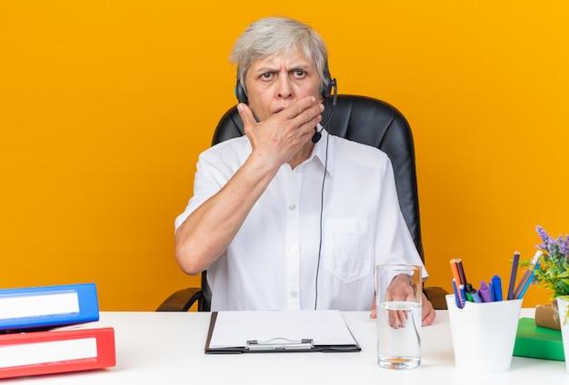 Geschokte blanke vrouwelijke callcenter-operator op een koptelefoon die aan het bureau zit met kantoorhulpmiddelen die de hand op de mond leggen