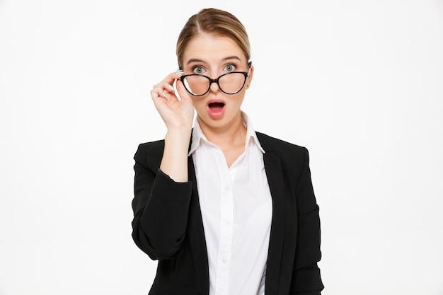 Geschokte blonde bedrijfsvrouw met open mond over wit